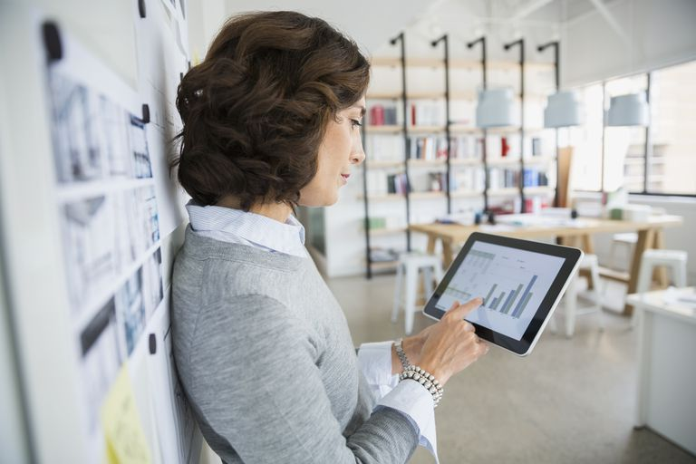 Architect viewing bar graph on digital tablet office
