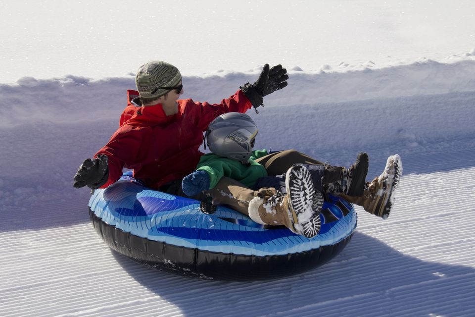 Father and son snow tubing on groomed path