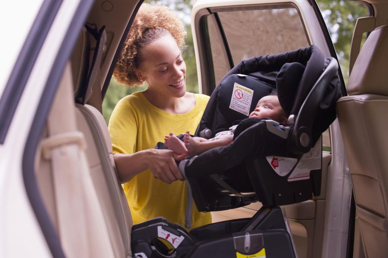 Mother loading baby into car seat