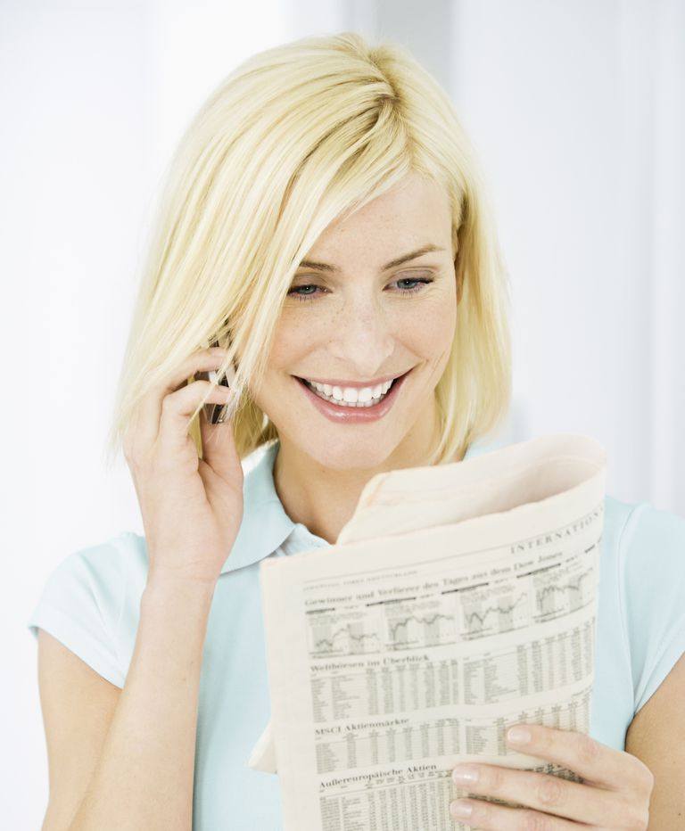 Woman Looking at Stock Market Pages
