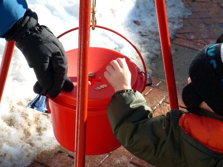 Child putting coins into a donation bucket