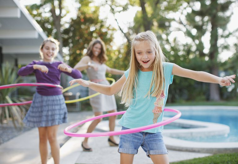 Mothers and daughters hula hooping outdoors