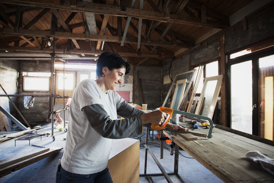 Woman using hacksaw