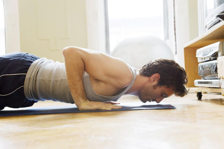 Man doing pushups or yoga in living room