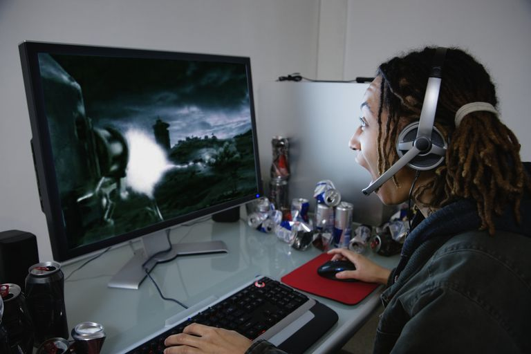 A young woman playing a desktop computer game, side view