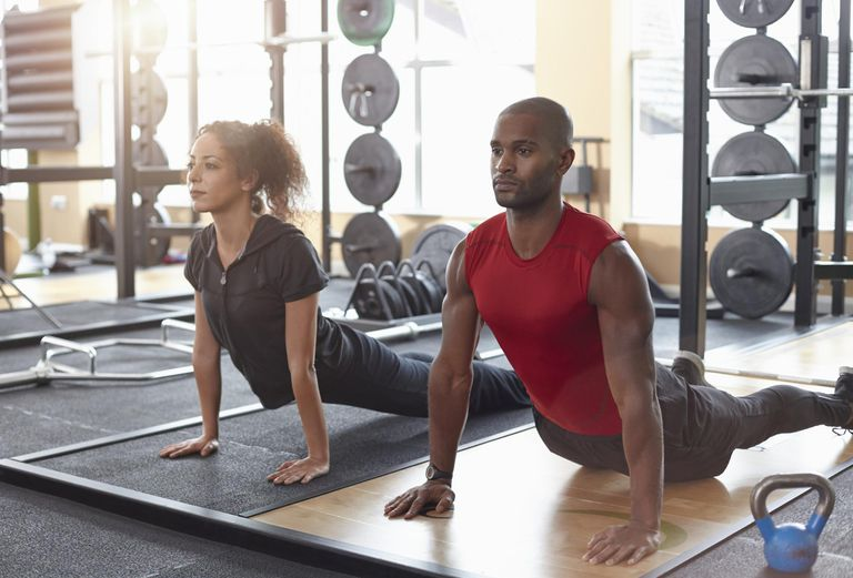 Man and woman doing yoga stretch in a gym