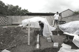 Wall foundations in landscaped garden with plastic sheeting covering new brick walls