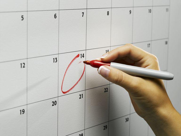 Woman Circling Day On Wall Calendar Close Up