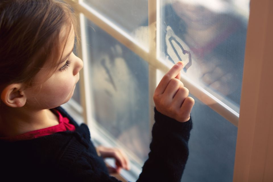 Girl drawing heart on fogged up window