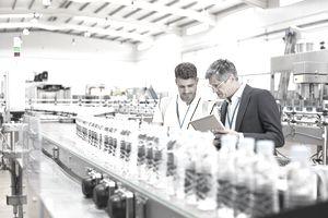 Supervisor and manager watching plastic bottles on conveyor belt