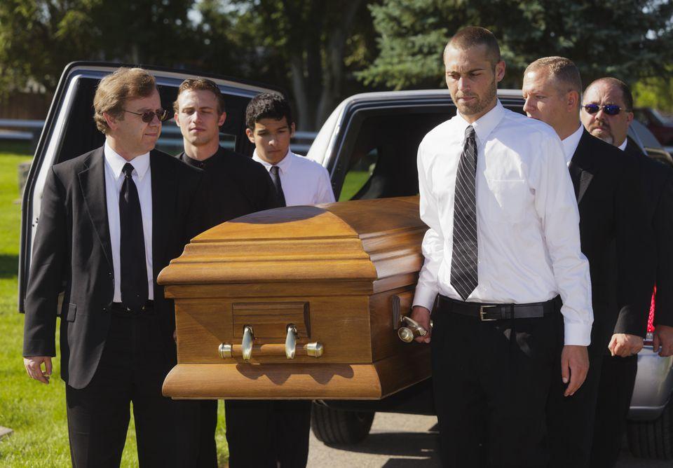 Pallbearers taking a casket out of a hearse