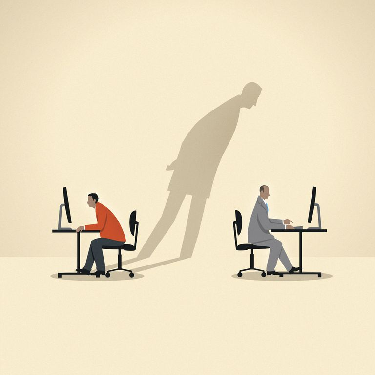 Shadow of businessman spying on colleague using computer