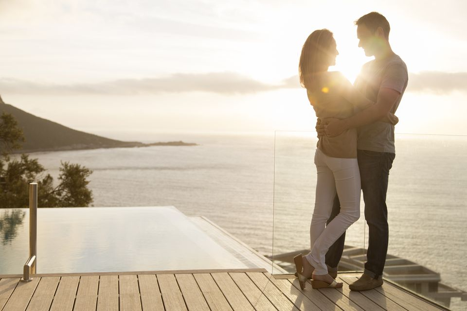 Couple on wooden deck overlooking ocean