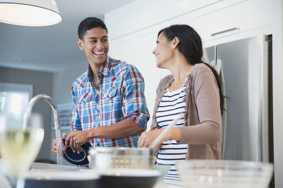 Happy couple looking at each other while washing dishes in kitchen