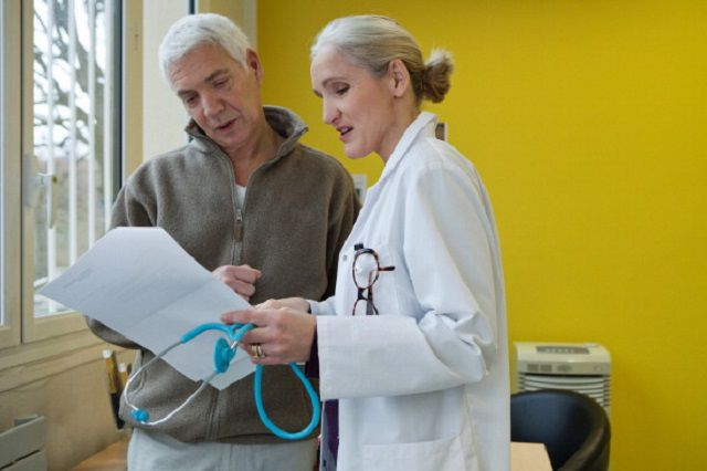 female talking to a patient about his concerns about Parkinson's disease