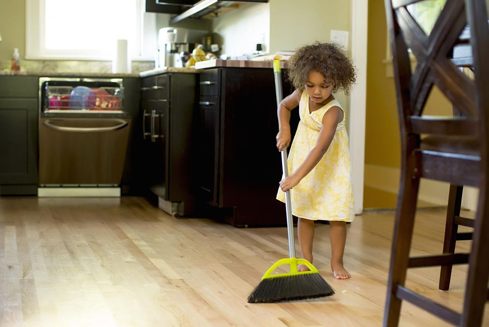Mixed race girl sweeping kitchen floor
