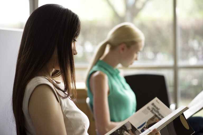 women reading magazines in office waiting room