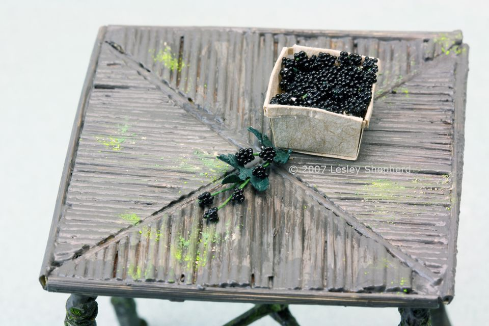 Photo of 1:12 scale miniature blackberries in a fruit basket and unpicked on the cane.