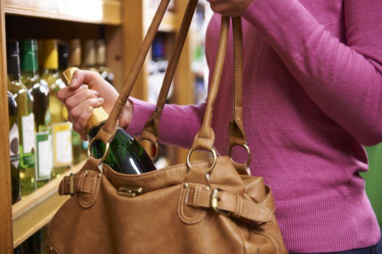 Woman Stealing Bottle Of Wine From Supermarket