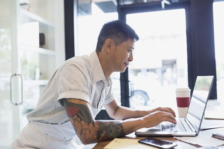 Bakery business owner working at laptop