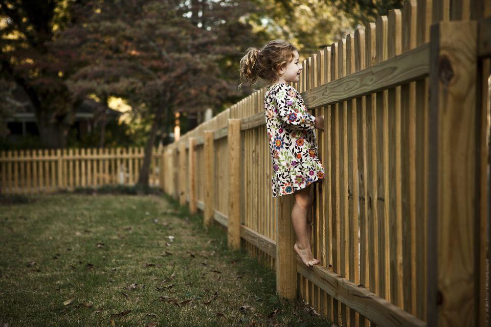 Little girl peeking over the fence
