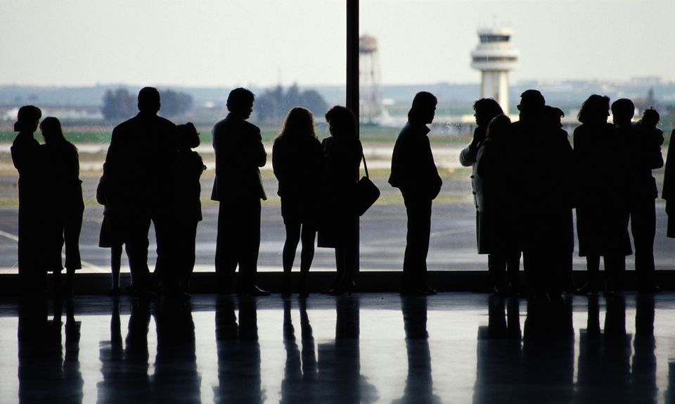 Silhouette of people standing by window in Seville Airport, Andalucia, Spain.