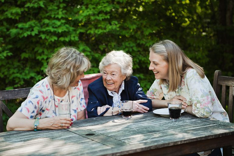 Three generations of women talking and laughing at a table