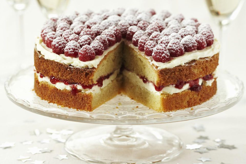 cake with raspberry on cakestand, white wine in background, close-up
