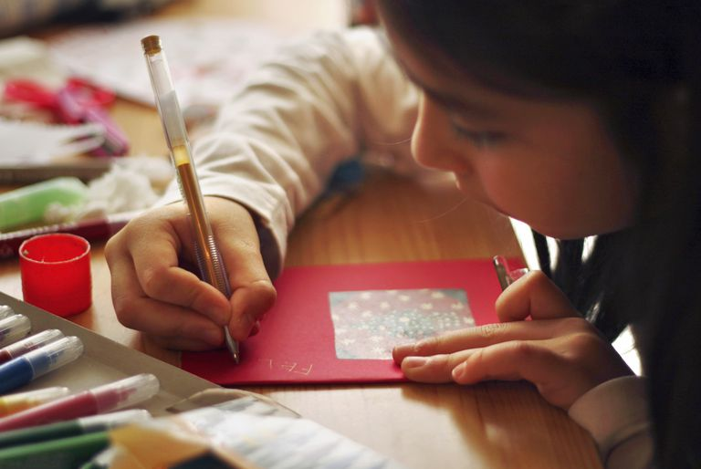 Close up of a girl's hand writing a postcard