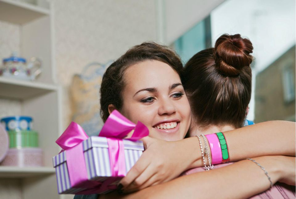 Young women holding birthday gift and embracing