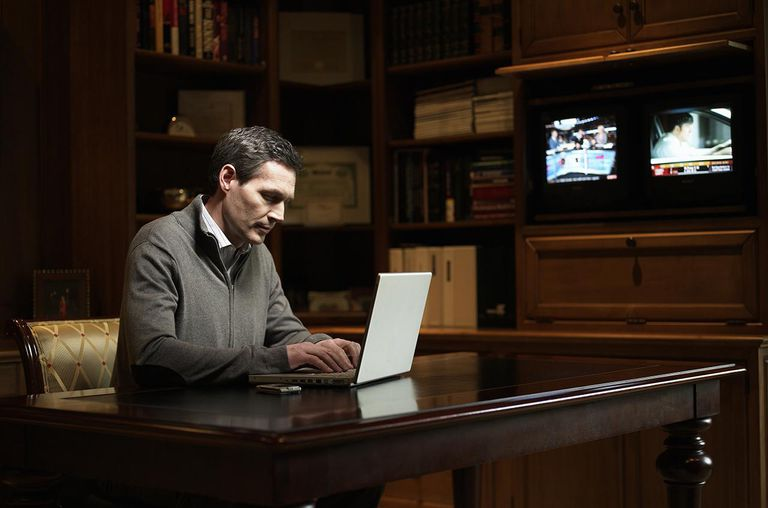 Mature man using laptop at desk in home office
