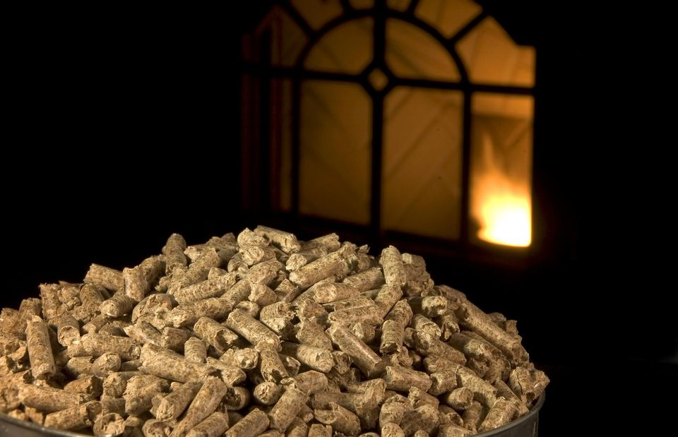 Wood pellets with pellet stove lit in background.