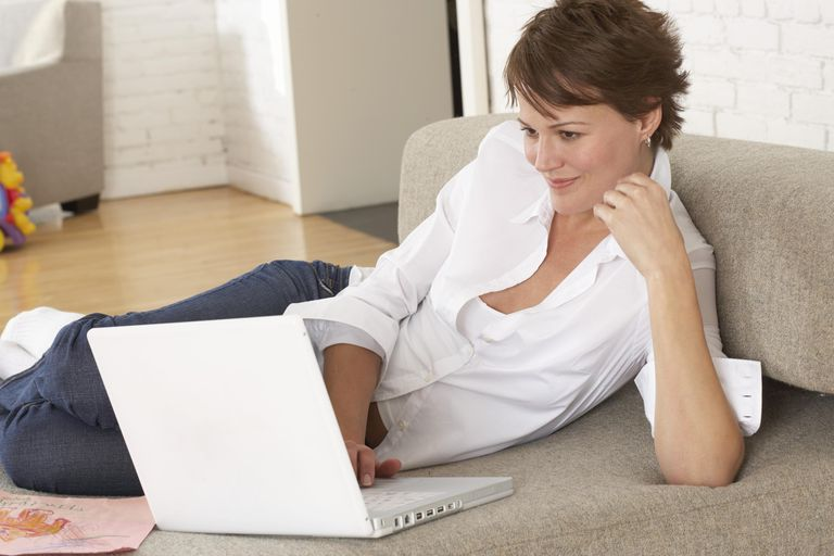 Woman sitting on floor in lounge room, using laptop