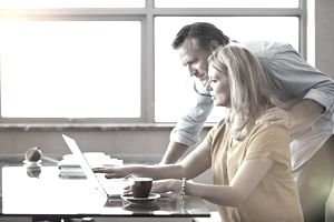 Couple working on finances at a computer in a sunlit room.