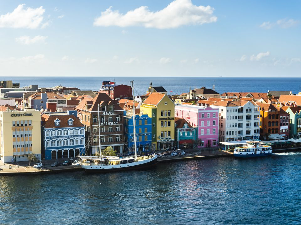 Curacao, Willemstad, Punda, schooner and colorful houses at waterfront promenade