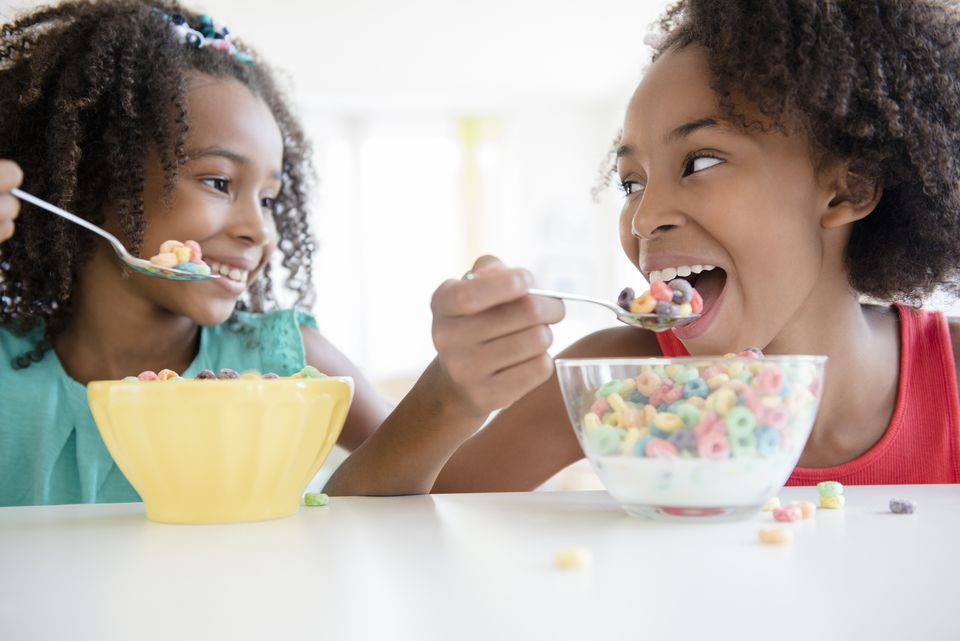 Mixed race sisters eating cereal