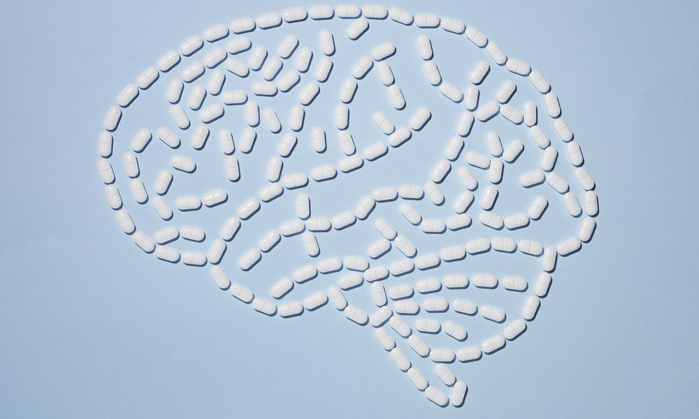 White pills are laid out in the shape of a brain.
