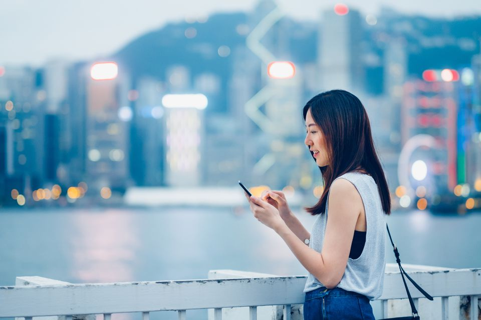 Smiling young lady using cell phone on urban rooftop, with illuminated city skyline as background
