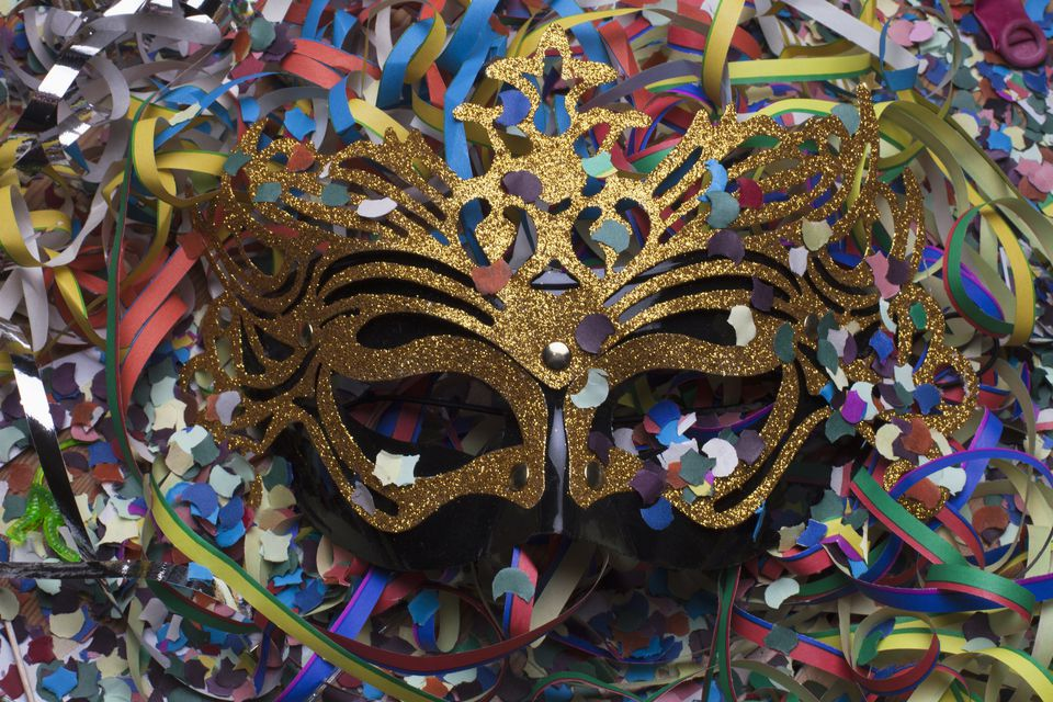 A masquerade mask nestled among confetti and streamers
