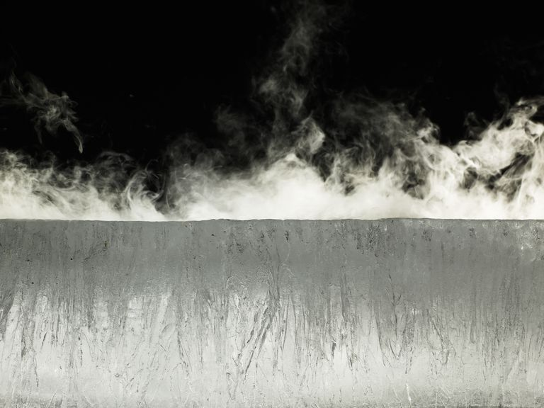Water vapor rising from block of ice. A volatile substance converts from liquid or solid into a vapor.