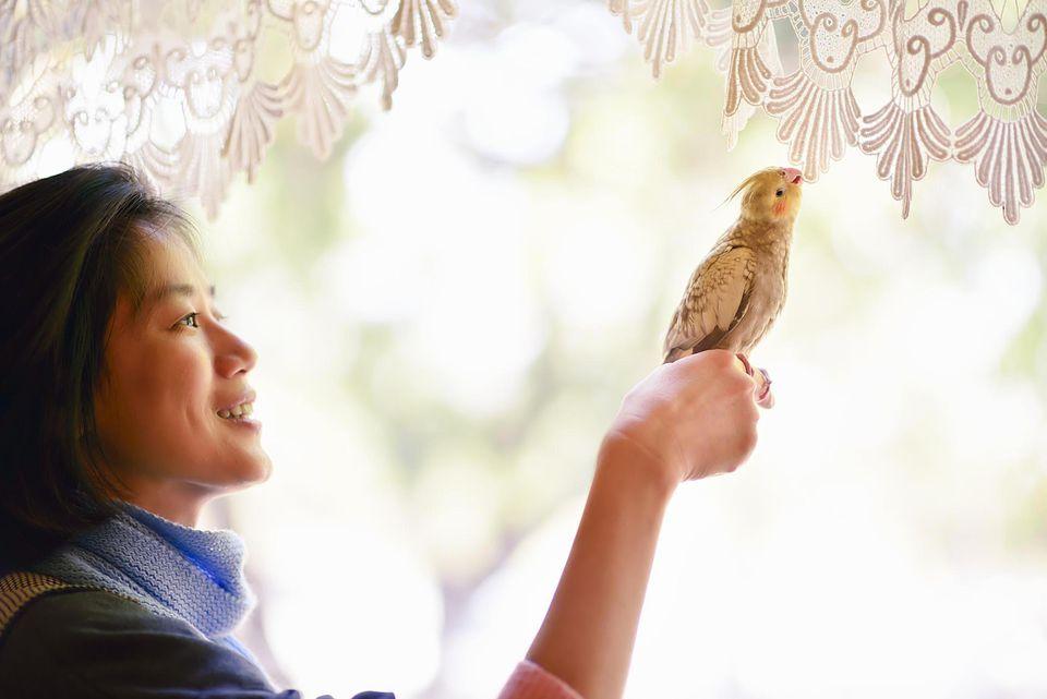 Cheerful woman and pet bird