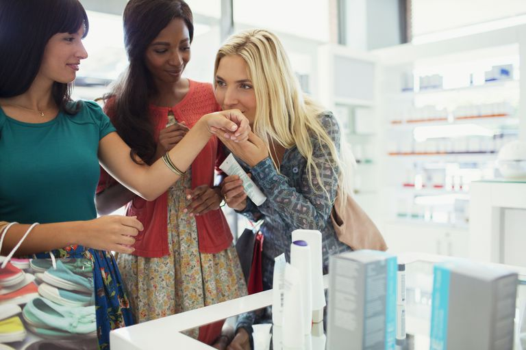 Women smelling perfume in drugstore