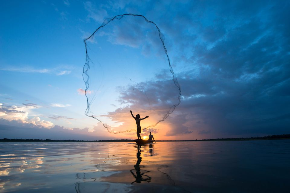 Vietnamese fisherman throws out a net at sunrise