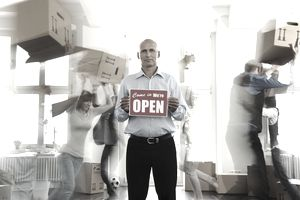 usinessman holding open sign in empty office