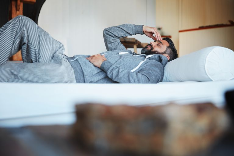 man resting on bed