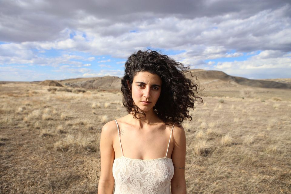 woman with curly brown hair standing in front of a landscape