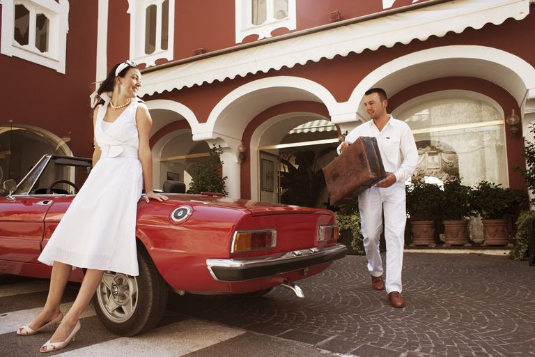 Man carrying woman's bags to car outside hotel