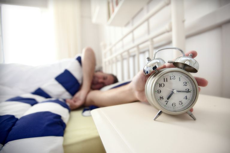 A man reaches to turn off his alarm clock