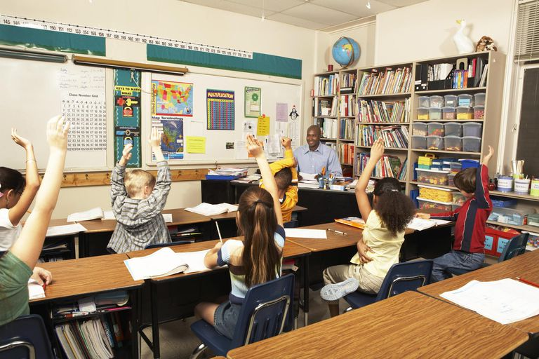 Schoolchildren (8-11) raising hands for teacher in classroom, rear view