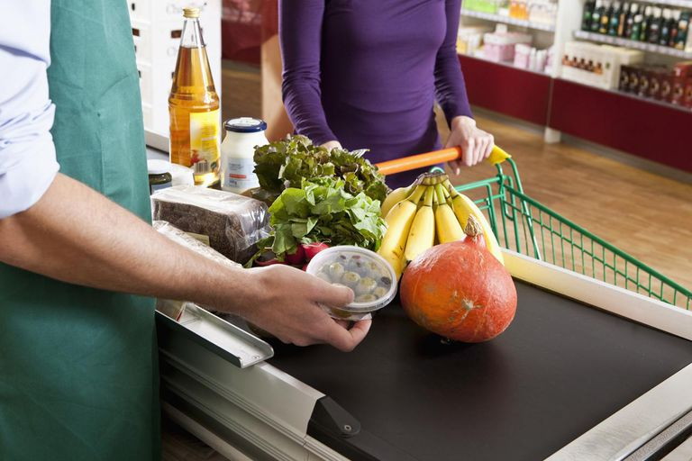 A cashier and customer at the checkout line of a supermarket, midsection